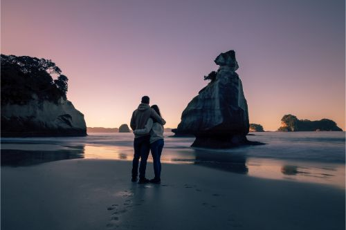 A couple looking out to sea at sunset - North Island hikes