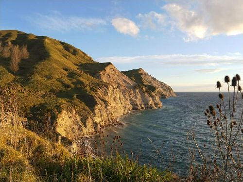 A landscape image of Mahia peninsula golden cliffs at sunset