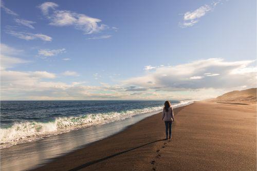 A girl walking down a black sand beach at sunset