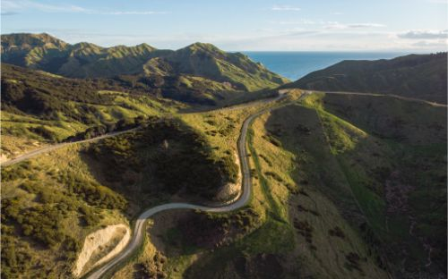 A drone landscape photo of a windy road cutting through the hills of Mahia Peninsula