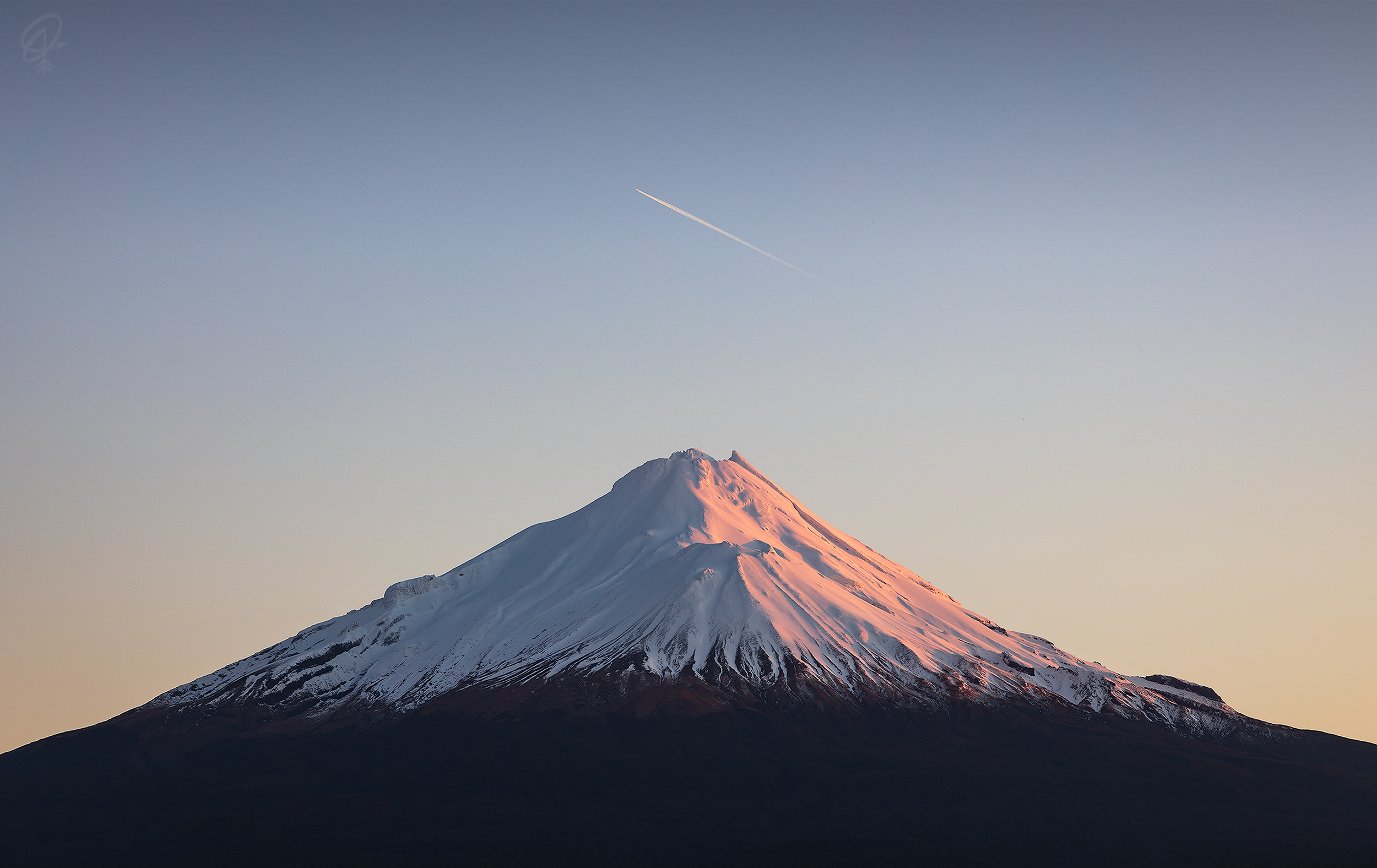 mt taranaki at sunrise with a plane flying over