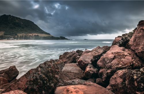 The view of Mount Maunganui with a storm looming above