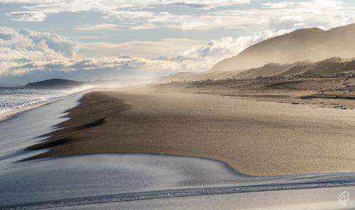 A black sand beach with waves crashing onto shore