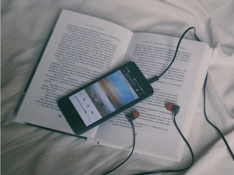Phone with headphones laid over a book